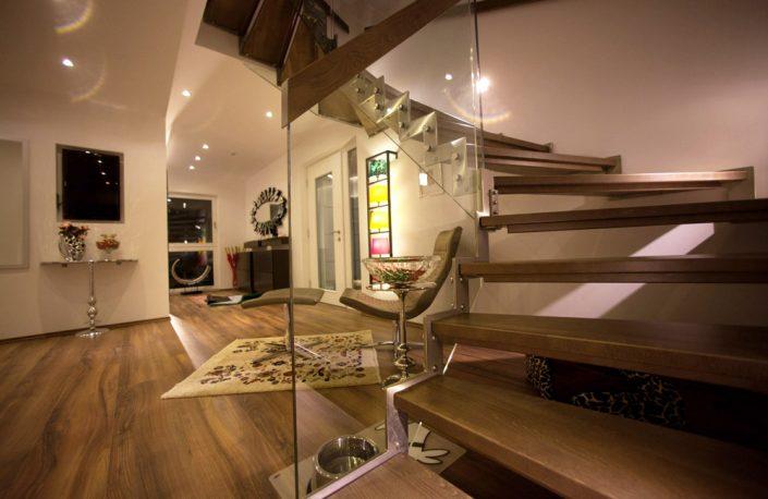 Designtreppe Artemis mit abgetreppter Edelstahlwange, Holzstufen und Glasgeländer