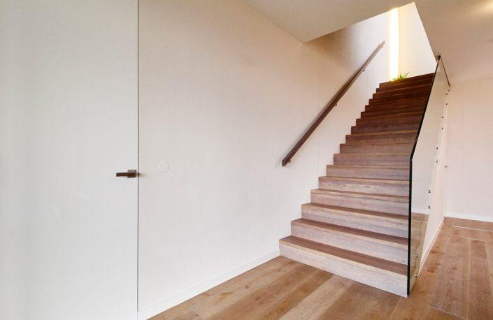 Treppenbelegung Kronos für Rohbau- und Betonstiegen in Eiche, wandbündige Innentür in Hochglanz